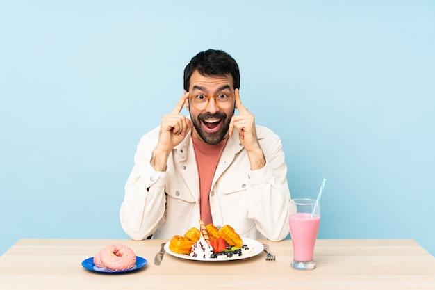 Человек за столом завтракает вафли и молочный коктейль в очках и удивлен