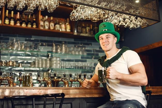 맥주와 함께 바에서 남자. guy는 성 패트릭의 날을 기념합니다. 녹색 모자에있는 남자.