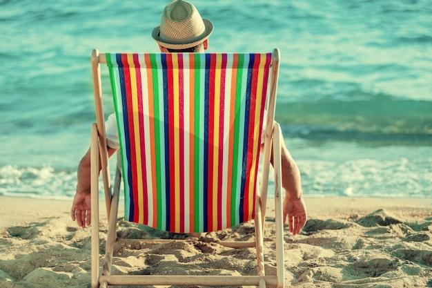 아름다운 해변에서 의자에 앉아 있는 남자, 뒷모습