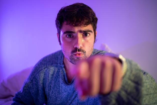 Мужчина в постели дает совет или приказывает жестом на камеру