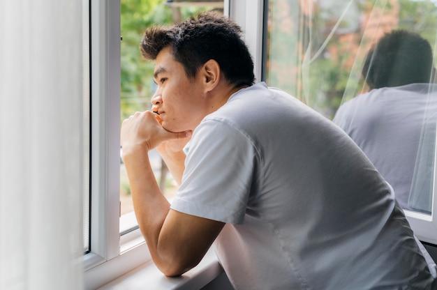 야외에서 창문을 통해보고있는 유행병 동안 집에서 남자