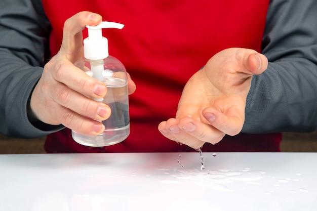 코로나 바이러스 전염병으로 집에있는 남자가 알코올 용액으로 손을 소독합니다.