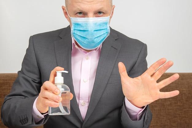 自宅で検疫中の男性が顔に医療用マスクを付けて、ウイルス感染によるアルコール溶液で手を消毒します。コロナウイルスの流行中の推奨事項。
