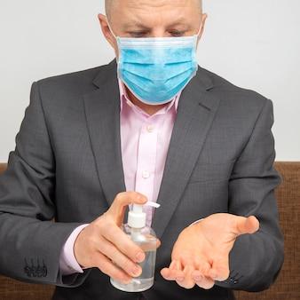 얼굴에 의료용 마스크를 쓴 집에있는 남자가 바이러스 감염으로 인한 알코올 용액으로 손을 소독합니다.