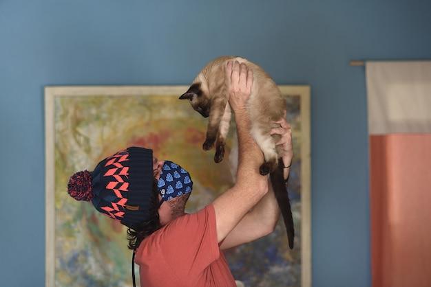 얼굴 마스크를 가진 집에서 남자는 그의 고양이와 연극