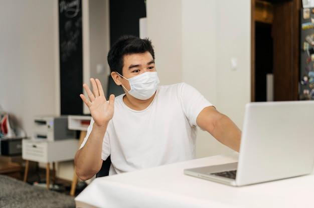 ラップトップで手を振っているパンデミックの間に医療マスクを持って家にいる男