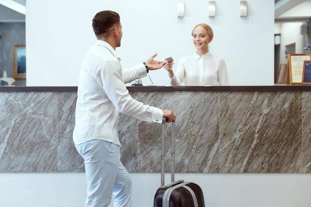 ホテルの受付で男。