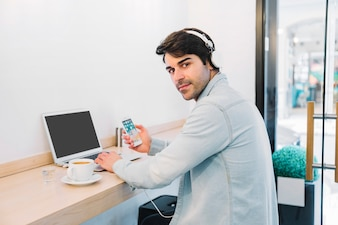 Man at laptop with smartphone and coffee