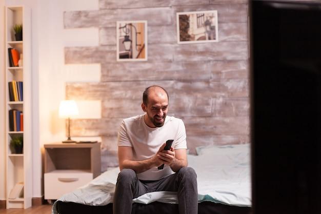 Человек ночью в пижаме смеется во время просмотра фильма по телевизору.