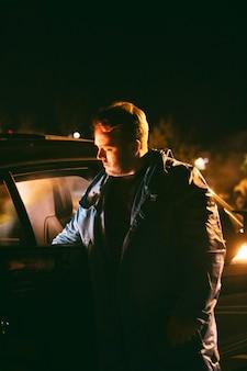 車の横に座っている夜の男
