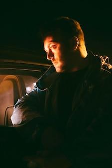Человек ночью сидит рядом с машиной