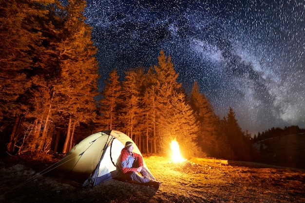 キャンプファイヤーとテントで夜の男