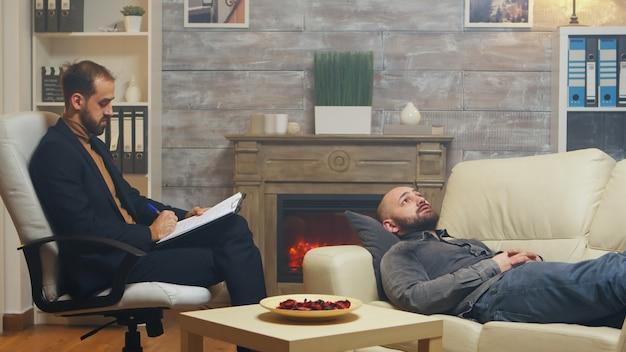 彼の離婚について話しているソファに横たわっている関係の専門家の男。