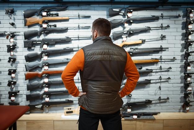 Мужчина у витрины с винтовками