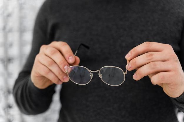 Человек в магазине примеряет очки крупным планом