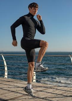 Мужчина на пляже тренируется в спортивной одежде