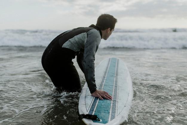 그의 서핑 보드와 함께 해변에서 남자