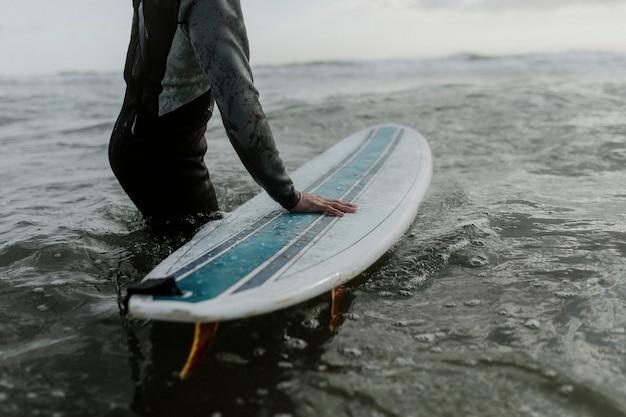 彼のサーフボードとビーチで男