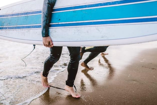 Человек на пляже со своей доской для серфинга