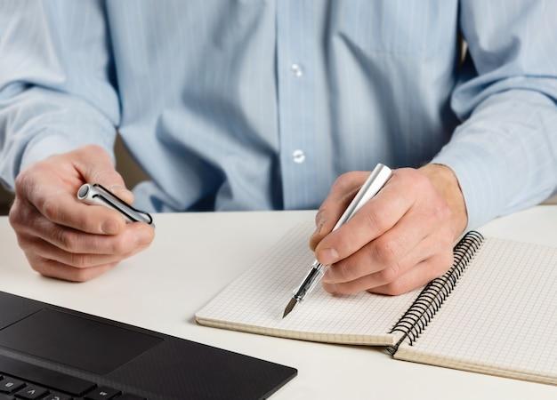 Человек за компьютером с чернильной ручкой.