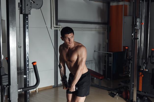 ジムの男。男は運動をします。スポーツ、パワー、ダンベル、緊張、運動-健康的なライフスタイルの概念。