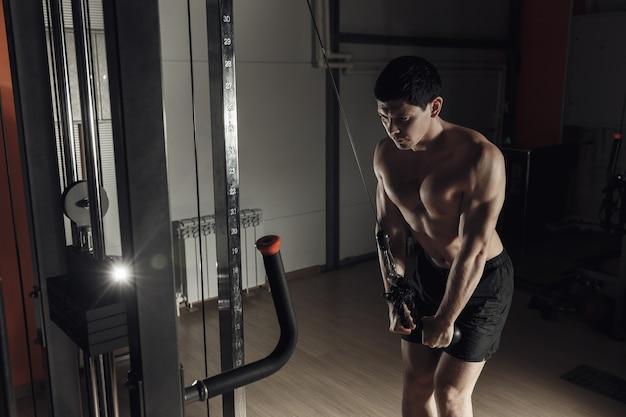 ジムの男がエクササイズスポーツパワーダンベルテンションエクササイズをする男
