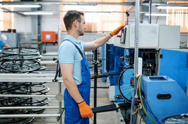 공작 기계의 남자가 공장에서 자전거 림을 확인합니다. 작업장에서 자전거 바퀴 조립, 사이클 부품 설치