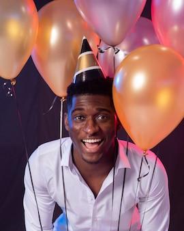 紙の円錐形の帽子をかぶっているパーティーの男