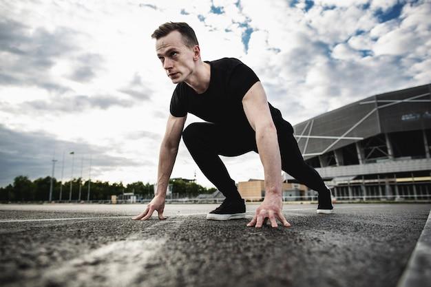 시작할 준비가 된 남자. 경기장 근처를 실행하는 젊은 선수 남자. 남자는 야외에서 훈련합니다. 마라톤 준비