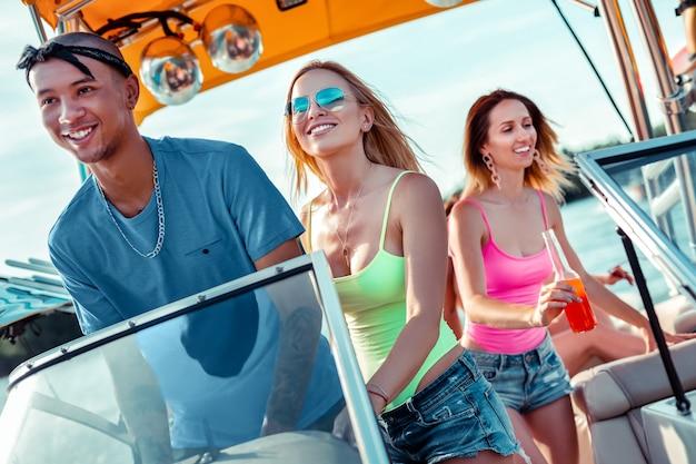 바퀴에 남자. 행복 한 젊은 남자와 그의 여자 친구는 앞서 찾고 유람선을 운전하는 동안 스티어링 휠에 서
