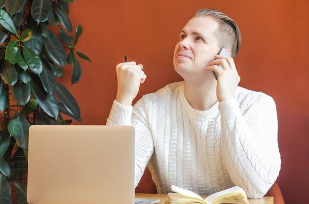 Человек на рабочем месте с компьютером разговаривает по телефону