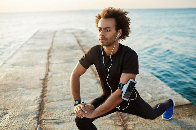 桟橋で突進ハムストリングストレッチ運動で足を伸ばして黒いスポーツウェアの男選手。イヤホンで音楽を聴く。