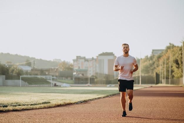 朝のスタジアムでジョギングする男アスリート