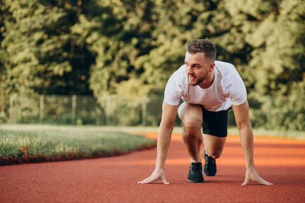 Atleta dell'uomo che fa jogging allo stadio al mattino