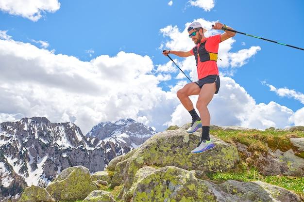 남자 선수는 산에서 트레일 운동을하는 동안 돌 사이에서 점프합니다.