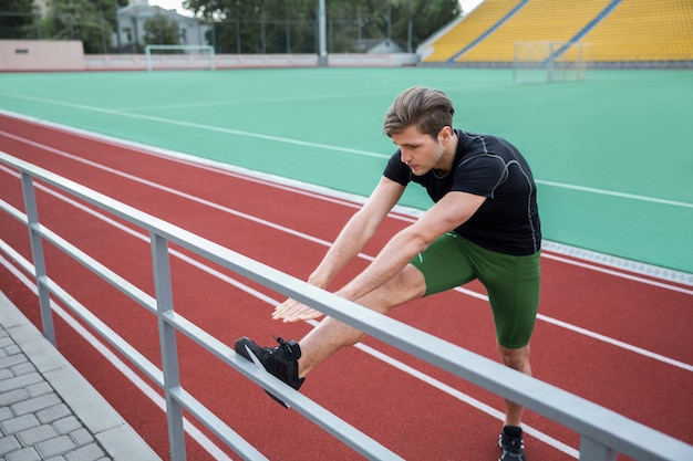Man athlete make stretching exercises outdoors
