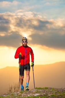 След спортсмена человека практикуя с палками на заходе солнца вертикальное изображение