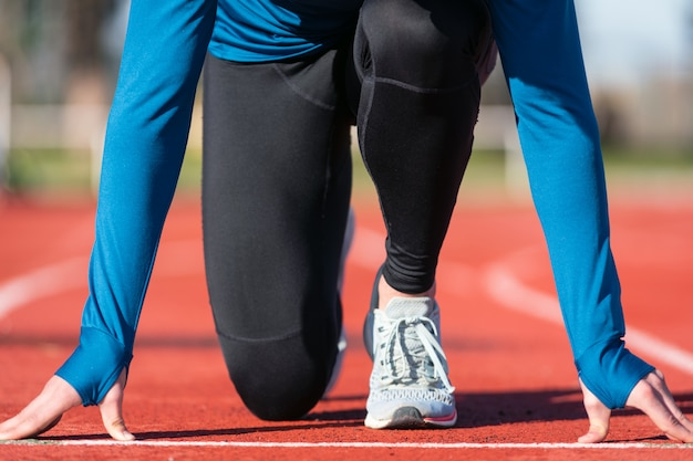Man athlete on the starting line of a running track at the stadium, close up.