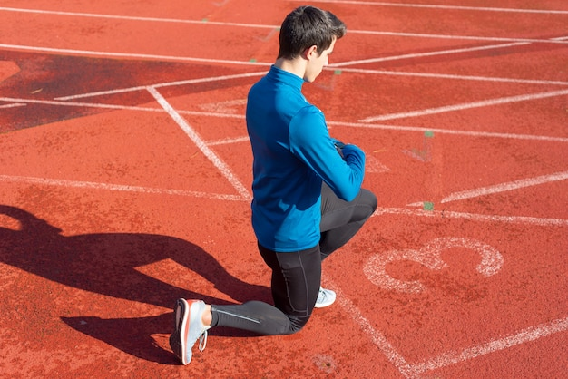 Man athlete on the starting line of a running track at the stadium, resting on his knees.