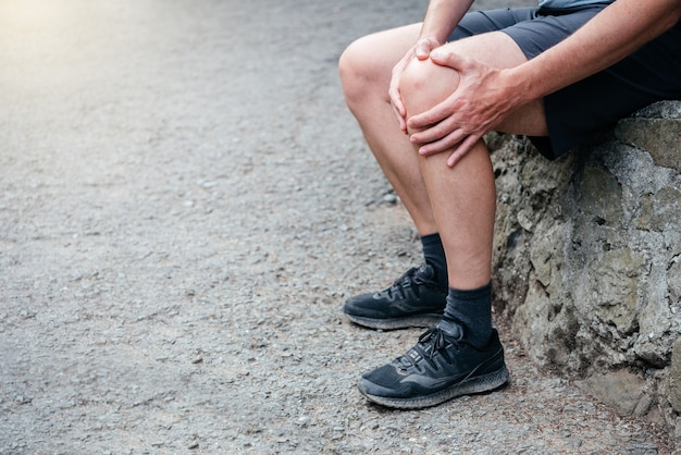 A man athlete suffering from knee pain through patellofemoral pain syndrome