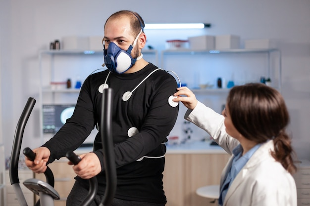 Man athlete with mask running on cross trainer after medical researcher attached electrodes to her body. physician using computer to controls ekg data showing on laboratory monitors, vo2 max test.