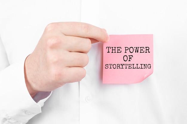Мужчина прикрепляет красную наклейку с надписью the power of storytelling к своей белой рубашке