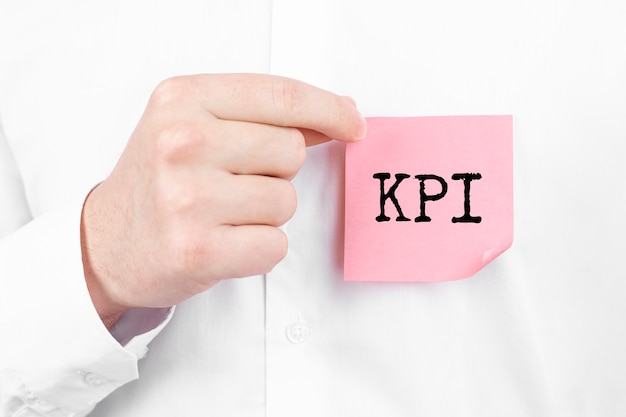 Man attaches a red sticker with text kpi overlay to his white shirt