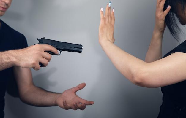 Мужчина напал на женщину с пистолетом на сером фоне