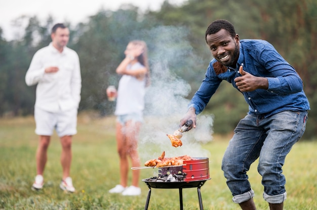 Man attending the barbecue and giving thumbs up