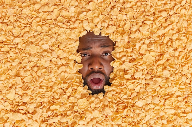 Man awakes very early going to have breakfast sticks head through dry cornflakes yawns and keeps mouth opened has healthy nutrition. human head buried in cereals