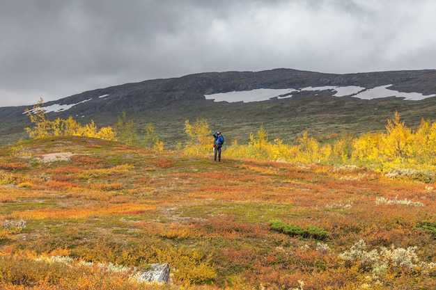 Man backpack hiker at kungsleden trail admiring nature of sarek in sweden lapland with mountains