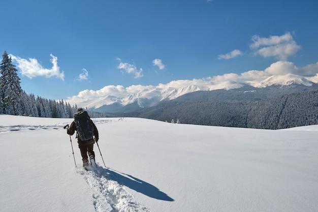 추운 겨울 날 눈 덮인 산 언덕을 하이킹하는 남자 백패커.