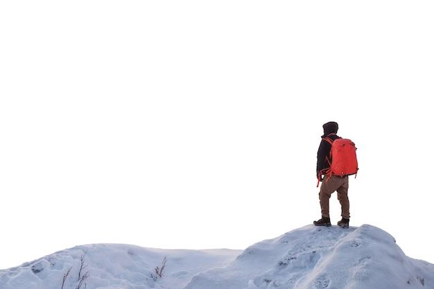 雪に覆われた尾根の丘の上に立っている男のバックパッカー。白い背景に