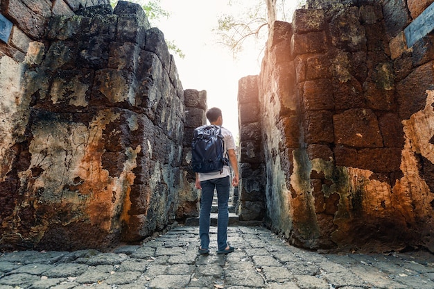 Man backpacker walking inside in prasat muang sing are ancient ruins of khmer temple in historical park